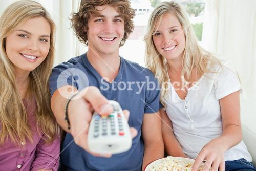 Focus shot on three friends as they use the remote to change the tv channel