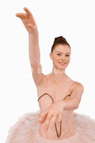Smiling ballerina with her arms extended