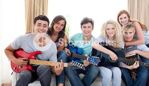 Group of teenagers playing guitar at home