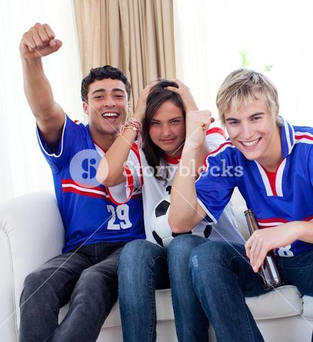 Adolescents watching a football match at home