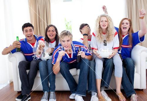 Teenagers watching a football match in the livingroom