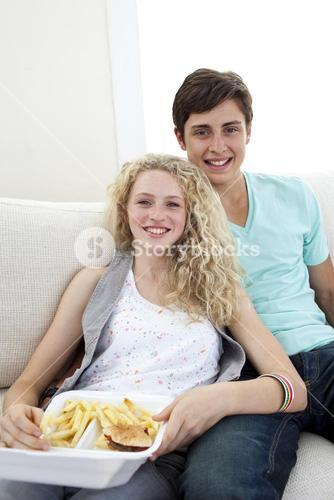 Teen couple eating burgers and fries