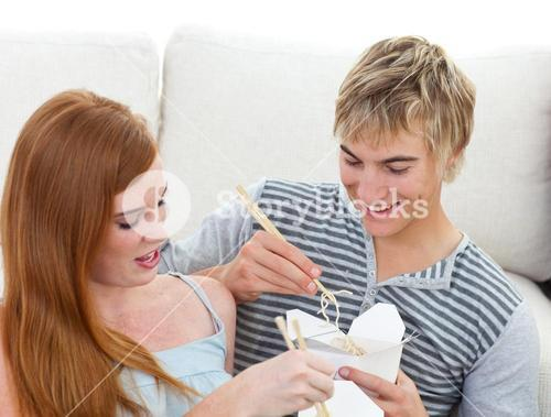 Couple of teenagers eating pasta