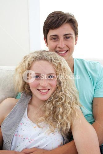 Portrait of teens couple sitting on the sofa