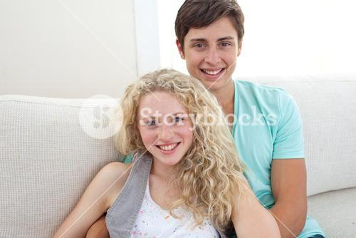 Happy couple of teens sitting on the sofa