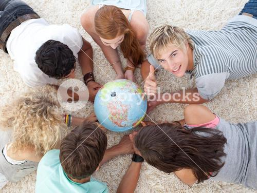 Group of teenagers on the floor examining a terrestrial world and a guy with thumb up