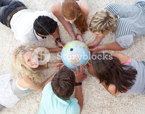 High angle of teenagers on the floor examining a terrestrial world