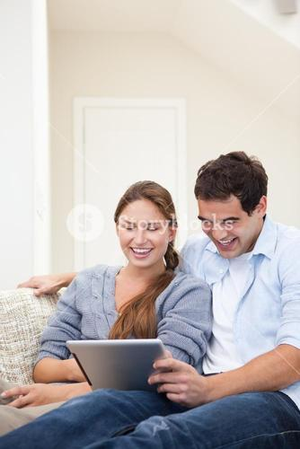 Couple laughing while holding a laptop
