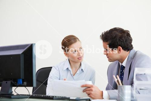 Colleagues talking while holding a sheet
