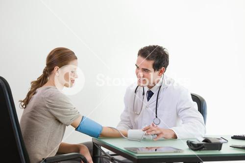 Doctor taking blood pressure of a patient