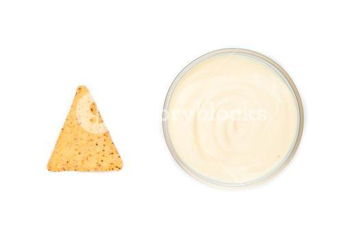A bowl of dip and a nacho placed side by side