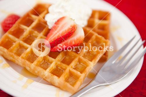 Waffles with whipped cream and strawberry on it