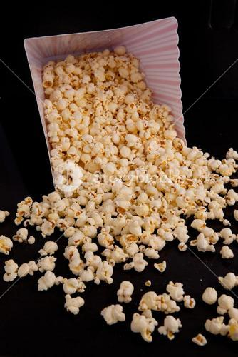 Many pop corn falling out of a box