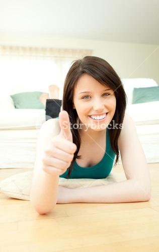 Happy woman with thumbs up lying on the floor