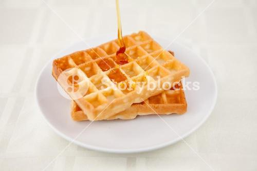 Honey falling on a waffle