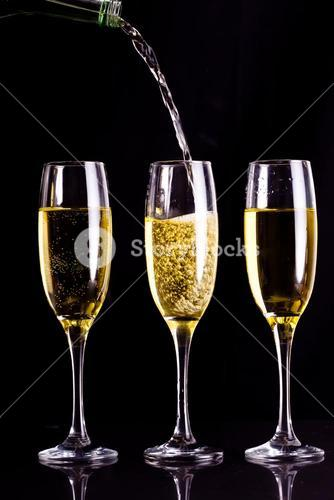Two full glasses of champagne and one being filled