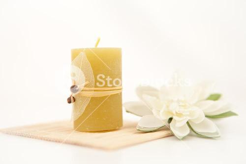Yellow candle with a white flower