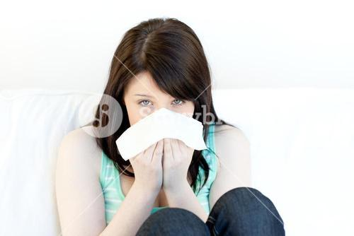 Portrait of a sick attractive woman blowing