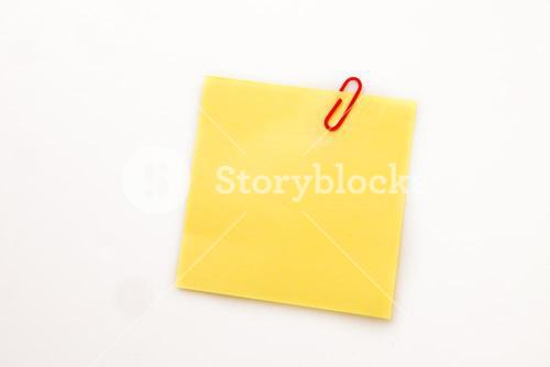 Yellow adhesive note with a paperclip