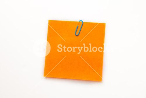 Orange adhesive note with a paperclip