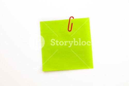 Green adhesive note with a paperclip