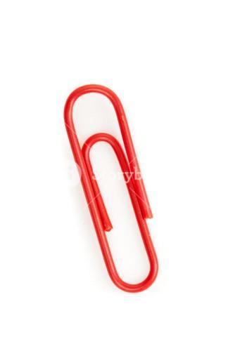 Close up of a red paperclip on the floor