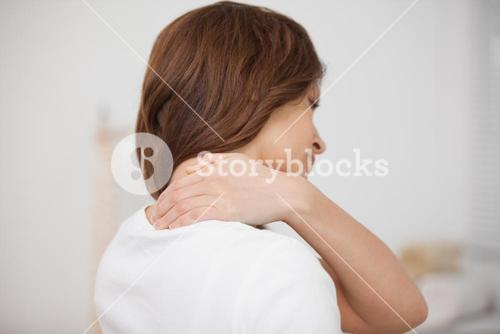 Brownhaired woman massaging her painful neck