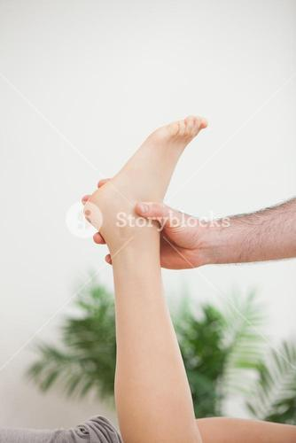 Doctor holding the foot of his patient