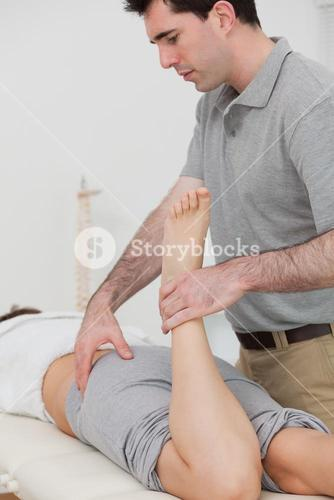 Woman lying while a physiotherapist is bending her leg
