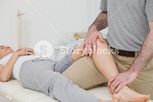 Woman lying on her back while a physiotherapist manipulates her leg