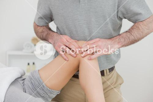 Woman lying with her legs folded while a man massaging her knee