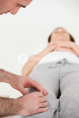 Woman lying on her back while a physiotherapist massing her knee