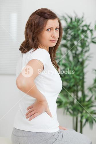Brownhaired woman touching her painful back