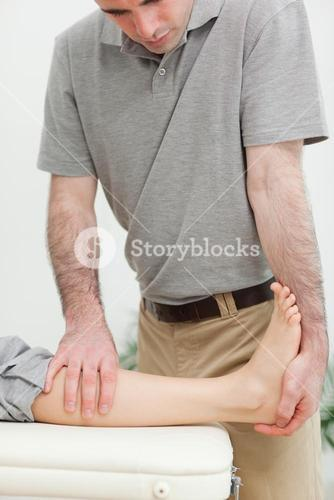 Serious physiotherapist stretching the leg of a patient