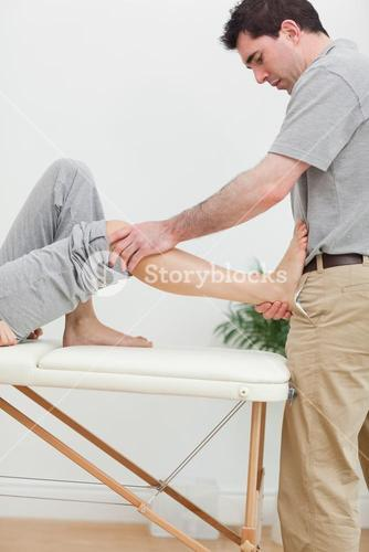 Brunette physiotherapist stretching a foot