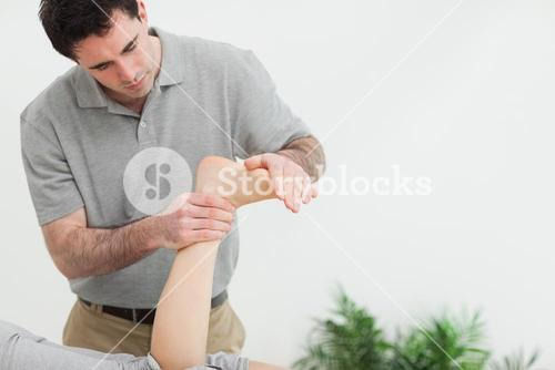 Brownhaired therapist stretching the foot of a patient