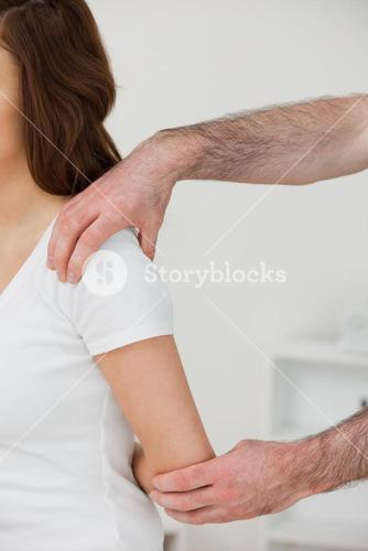 Close up of a doctor examining the shoulder of a patient