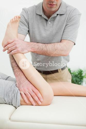 Close up of a men stretching the leg of a woman