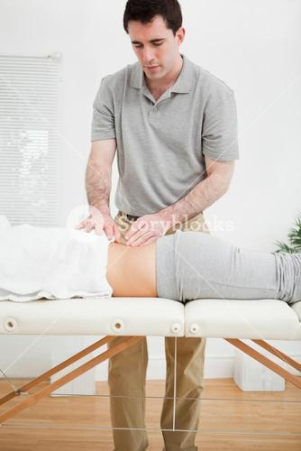 Brunette masseur standing while massaging the back of a woman