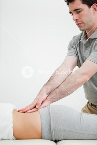 Close up of a masseur massaging the back of a woman