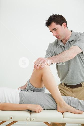 Serious physiotherapist stretching a leg while standing