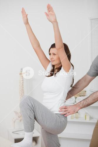 Woman doing exercise while a man is putting his hands on her hips