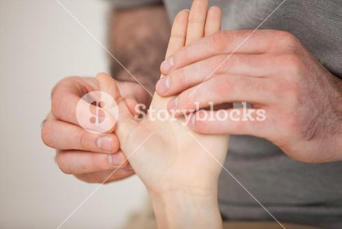 Thumb being massaged by a doctor