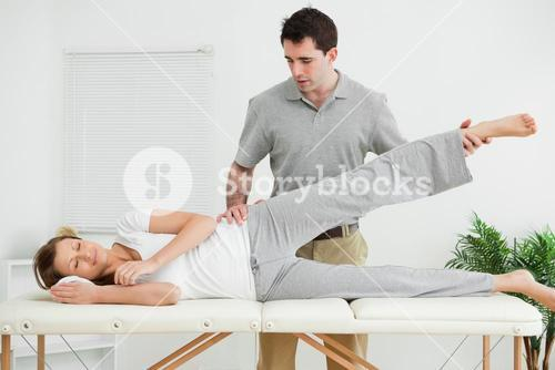 Serious practitioner rising the leg of his patient