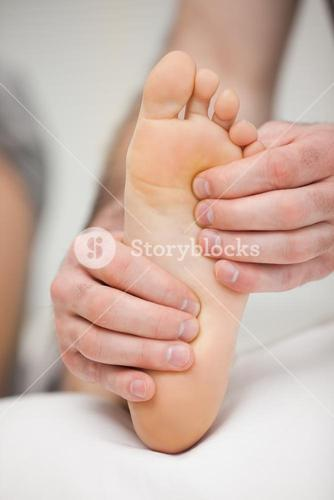 Fingertips touching the sole of a foot