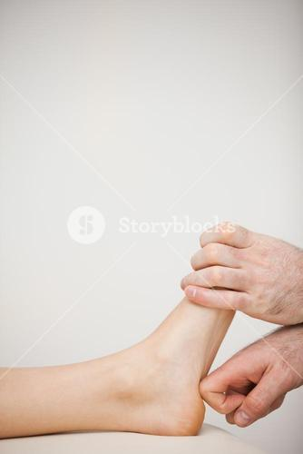 Chiropodist using his index finger to massage a foot