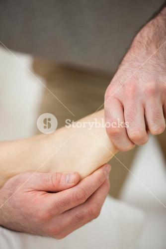 Barefoot being stretched by a doctor
