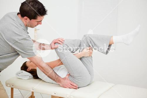 Woman holding her leg while being manipulated