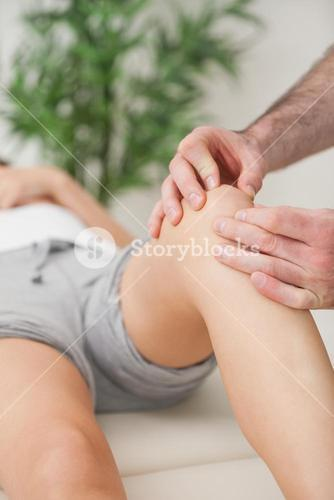 Fingers of a doctor massaging a leg