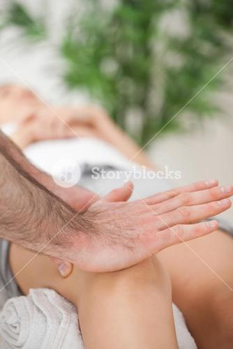 Osteopath using his hand palm to massage a knee